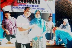 PEDULI : Rakhmad saat memberikan paket beras kepada masyarakat