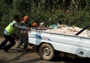 PEDULI : Anggota Polsek Montong dan masyarakat bahu-membahu mendorong kendaraan yang muat tanah uruk jalan