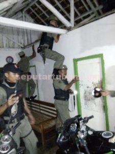 KERJA KERAS : Petugas Sat Pol PP saat memeriksa tiap kamar hingga menaiki dinding