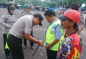 SIAGA LANTAS : Kapolres Tuban, AKBP Fadly Samad saat mengenakan rompi kepada salah satu perwakilan abang becak