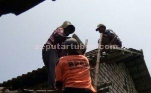 BANTU WARGA : Personil BPBD Pemkab Tuiban saat membantu memperbaiki atap rumah warga yang rusak