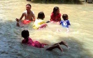 TETAP RIANG : Anak-anak Desa Kebomlati tetap ceria ditengah banjir merendam desanya