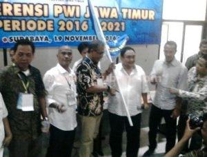 SEMANGAT TERBARUKAN : Ketua PWI Pusat, Margiono menyerahkan panji PWI kepada Ketua PWI Jatim terpilih, Akhmad Munir sebagai tanda pengukuhan