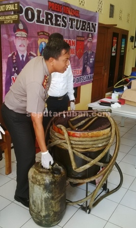 PELANGGARAN MIGAS : Kapolres Tuban, AKBP Fadly Samad menunjukkan sebagian barang bukti solar ilegal