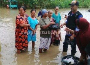 BERBAGI : Koordinator Pendekar Siaga, Hery Prasetyo dibantu seorang warga membagikan bantuan