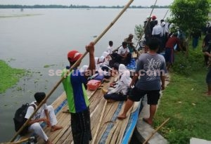 SEMANGAT MEMBARA : Para siswa saat pulang sekolah harus menaiki perahu karena menuju rumahnya jalan raya terendam dan tidak dapat dilalui